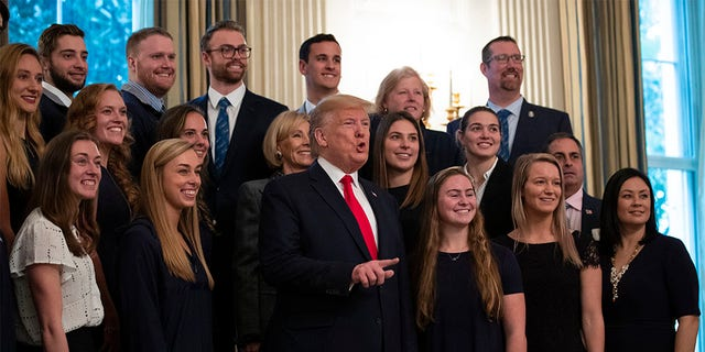 President Donald Trump stands with members of Queens University of Charlotte Swim Team during the NCAA Collegiate National Champions Day at the White House, Friday, Nov. 22, 2019, in Washington.