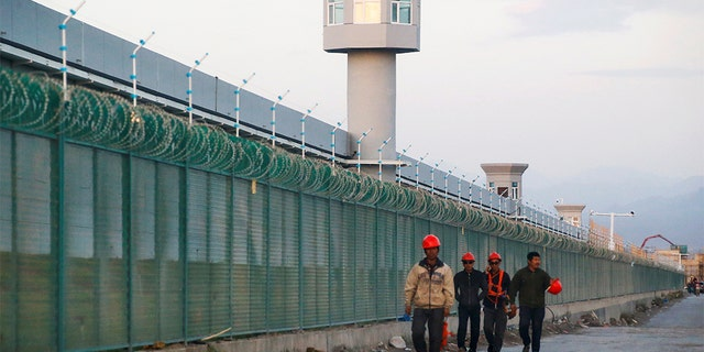 FILE: Workers walk by the perimeter fence of what is officially known as a vocational skills education center in Xinjiang Uighur Autonomous Region, China September 4, 2018.