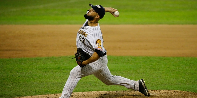 Leones de Caracas' pitcher Carlos Quevedo throws to Tigres of Aragua during the opening winter league baseball game in Caracas, Venezuela, Tuesday, Nov. 5, 2019. The Winter League is one that many major league players use to hone their skills in the offseason, and baseball is part of Venezuela's national fabric. (AP Photo/Ariana Cubillos)