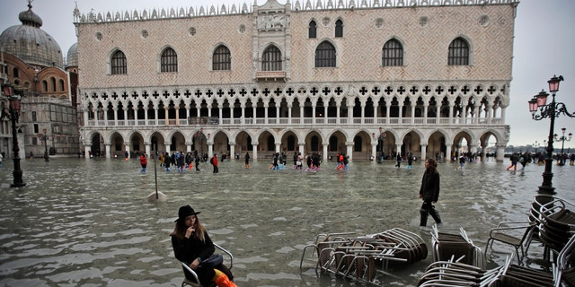 A woman sits in a chair in a flooded St. Mark's Square, in Venice, Wednesday, Nov. 13, 2019.