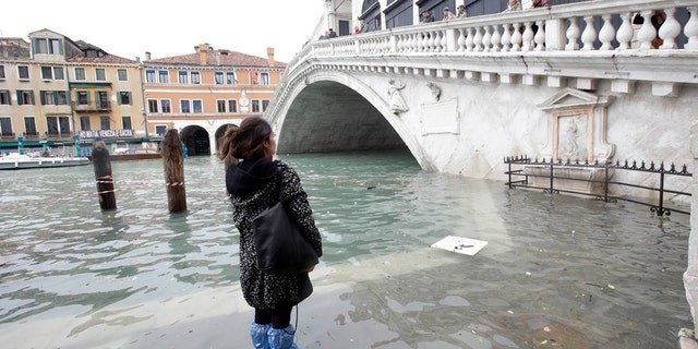 A woman looks at the Rialto Bridge during high water, in Venice, Wednesday, Nov. 13, 2019.