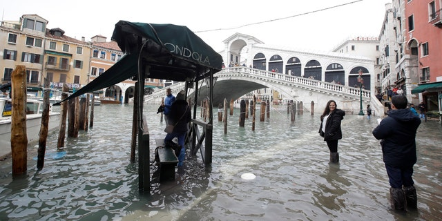 Tourists take pictures in front of the Rialto Bridge while wading through high water, in Venice, Wednesday, Nov. 13, 2019.