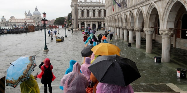 People walk on catwalk set up on the occasion of a high tide, in a flooded Venice, Italy, Tuesday, Nov. 12, 2019.