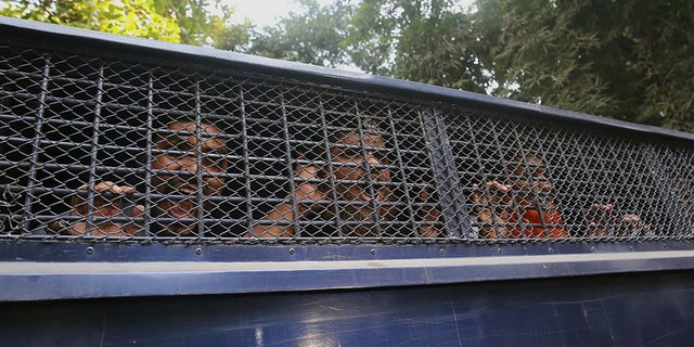 Members of the militant group shout slogans from inside a police van after their sentence was announced Wednesday. (AP)