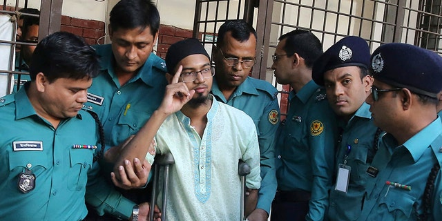 Police escort a member of a banned militant group after he was sentenced to death for an attack on a cafe that killed more than 20 people in Dhaka, Bangladesh, in 2016. (AP)