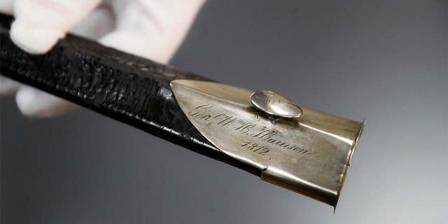Hamilton County Sheriff Jim Neil points out the engraving 'Gen. W. H. Harrison' on the scabbard of the sword Wednesday. (AP Photo/John Minchillo)