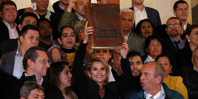 Surrounded by fellow lawmakers, Añez, center, holds a Bible after she declared herself the country's interim president during a session at Congress in La Paz on Tuesday. (AP Photo/Juan Karita)
