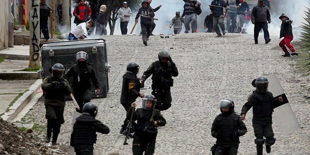 Supporters of former President Evo Morales clash with police in La Paz on Monday. (AP Photo/Juan Karita)