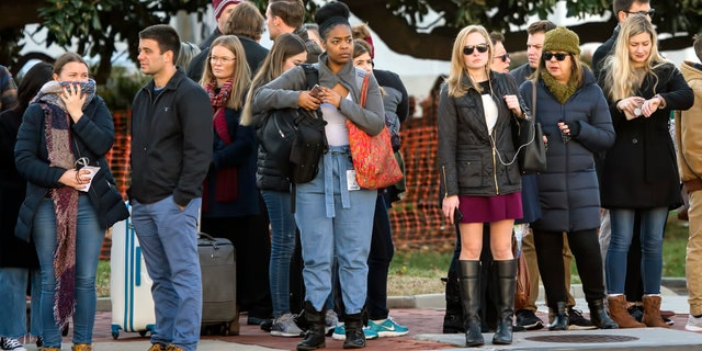 People wait near the U.S. Capitol and congressional office buildings Tuesday. (AP Photo/J. Scott Applewhite)