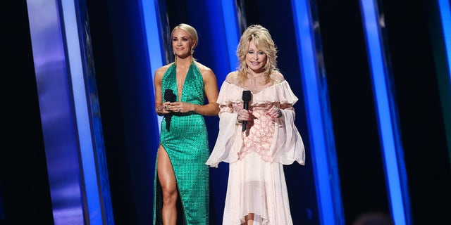 NASHVILLE, TENNESSEE - NOVEMBER 13: (FOR EDITORIAL USE ONLY) Carrie Underwood (L) and Dolly Parton speak onstage during the 53rd annual CMA Awards at the Bridgestone Arena on November 13, 2019 in Nashville, Tennessee. (Photo by Terry Wyatt/Getty Images,)