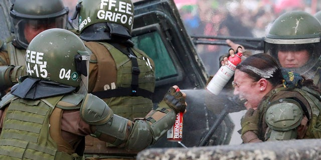 A riot police officer that was on fire is assisted by colleagues during a protest against Chile's government in Santiago, Chile, Nov. 4.