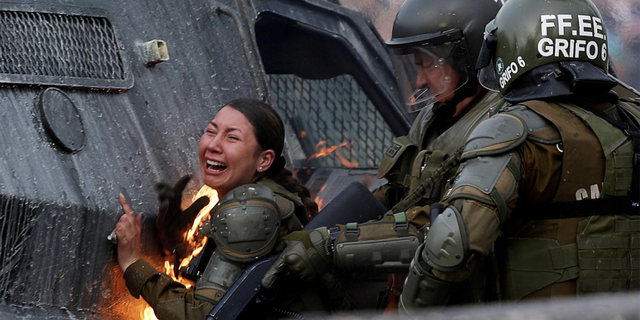 A riot police officer on fire reacts during a protest against Chile's government in Santiago, Chile