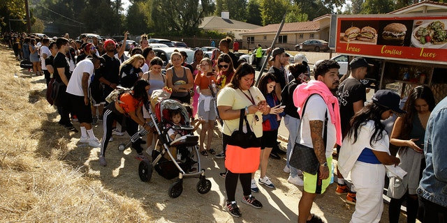 People line up around the block of singer Chris Brown's home in the Tarzana area of Los Angeles Wednesday, Nov. 6, 2019.