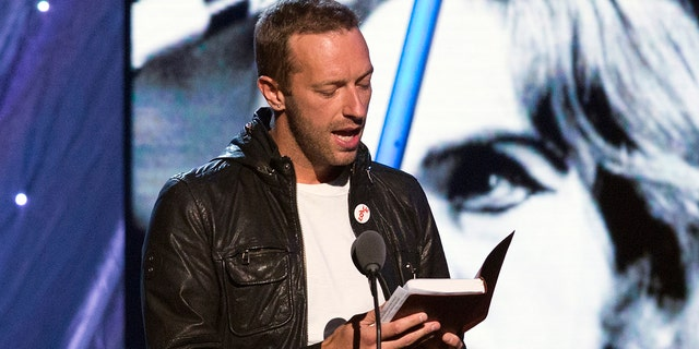 Coldplay lead vocalist Chris Martin reads from a Bible while inducting Peter Gabriel into the Rock and Roll Hall of Fame in 2014. REUTERS/Lucas Jackson