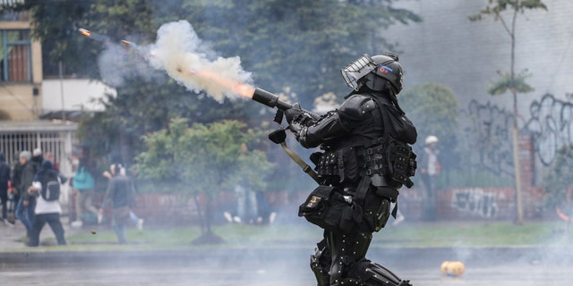 A police officer fires tear gas at anti-government protesters in Bogota, Colombia, Thursday, Nov. 21, 2019. (AP Photo/Ivan Valencia)