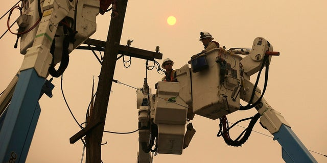 Nov. 9, 2018: Pacific Gas & Electric crews work to restore power lines in Paradise, Calif. (AP Photo/Rich Pedroncelli)
