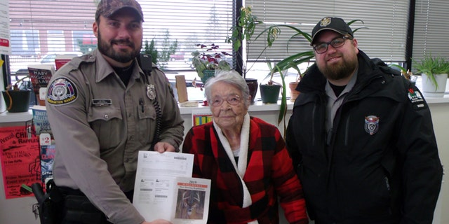 Florence poses with DNR Wardens after purchasing her first gun deer license.