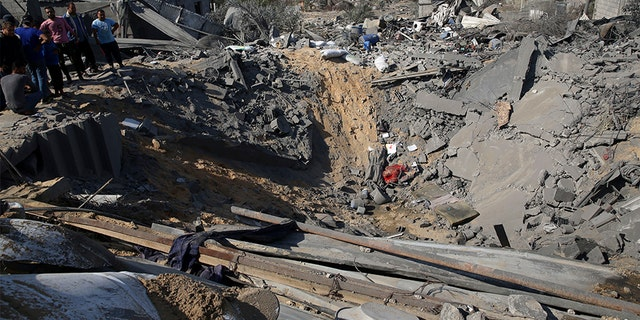 Palestinians inspect a crater and the rubble of destroyed houses following Israeli missile strikes, in Al-Qarara, east of Khan Younis, earlier this week.