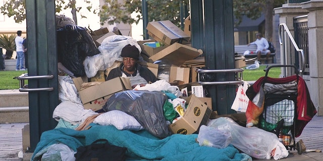 A homeless woman sits at a bus stop in Oakland, surrounded by her belongings. (Credit: Gabe Nazario/Fox News)