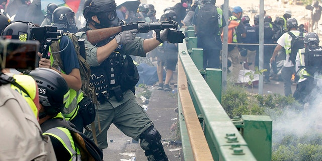 A police officer prepares to fire tear gas canisters during a clash with protesters near the Hong Kong Polytechnic University in Hong Kong on Monday. (AP)