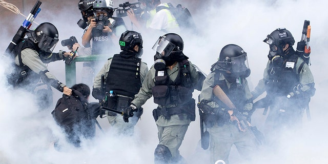 Police in riot gear move through a cloud of smoke as they detain a protester at the Hong Kong Polytechnic University on Nov. 18.