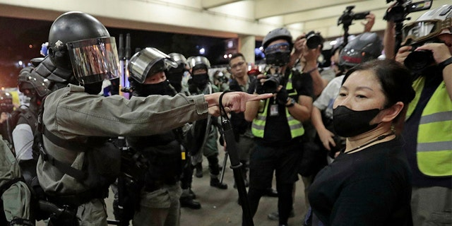 Police in riot gear ask a woman to take off her mask outside a train station in Hong Kong, on Nov. 3. (AP)