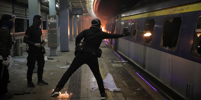 Students continued the 5-month-old anti-government movement. Some hurled Molotov cocktails at a parked train on a university campus. (AP Photo/Kin Cheung)