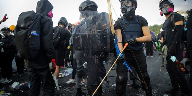 Students wielded homemade gear and weapons outside the Chinese University of Hong Kong on Wednesday.  (AP Photo/Kin Cheung)
