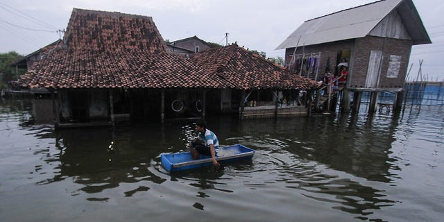 DEMAK, INDONESIA FEBRUARY 2: A man uses a handmade boat to reach his water-logged home in Sriwulan village, Sayung sub-district of Demak regency, Central Java, Indonesia on February 2, 2018.