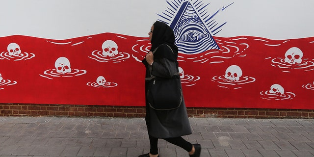 An Iranian woman walks past a new mural painted on the walls of the former US embassy in the capital Tehran on November 2, 2019. (Photo by ATTA KENARE / AFP) (Photo by ATTA KENARE/AFP via Getty Images)