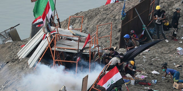 Iraqi security forces use tear gas to disperse anti-government protesters in Baghdad, Iraq, Wednesday, Oct. 30, 2019. Anti-government protests in Iraq gained momentum Wednesday with tens of thousands of people gathered in a central square in Baghdad and across much of the country's Shiite-majority central southern provinces. (AP Photo/Hadi Mizban)