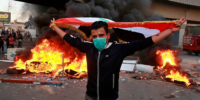A protester holds an Iraqi flag during demonstrations in Baghdad on Monday. (AP)