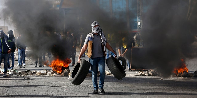 Palestinian demonstrators burn tires as they clash with Israeli troops during the protest against the U.S. settlement policy shift at checkpoint Beit El near the West Bank city of Ramallah, Tuesday.
