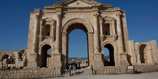 Tourists pass through the Arch of Hadrian, built during the Roman Empire, and the South Gate of the well preserved Ancient Roman city of Gerasa, in the city of Jerash, Jordan, in 2015.