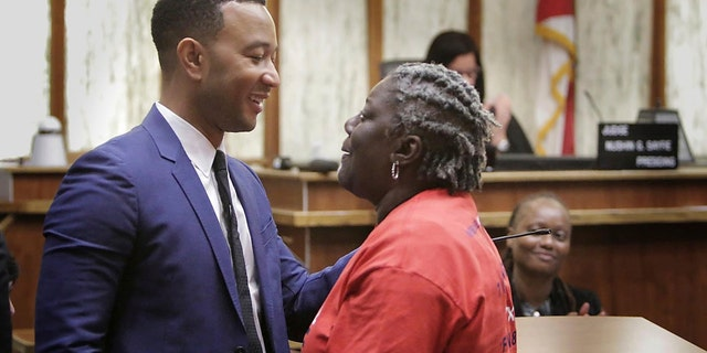 Singer songwriter John Legend, left, greets Carmen Brown who was the first person called up in a special court hearing aimed at restoring her right to vote under Florida's amendment 4, Friday, Nov. 8, 2019, in Miami.