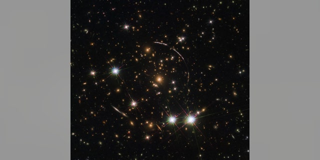 """The Hubble Space Telescope recently captured 12 mirror images of the distant, gravitationally-lensed Sunburst Arc. The galaxy can be seen here in this """"kaleidoscope"""" image distributed across four arcs (the elongated lines). (Credit: NASA, ESA and E. Rivera-Thorsen (Institute of Theoretical Astrophysics Oslo, Norway))"""