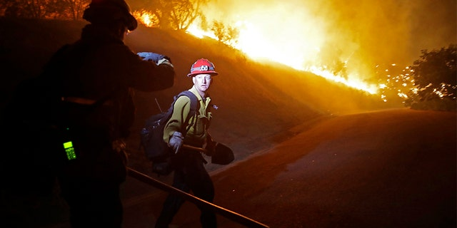 Firefighters walk on a road leading to a residence as the Maria Fire burns on a hillside Thursday, in Somis, Calif.