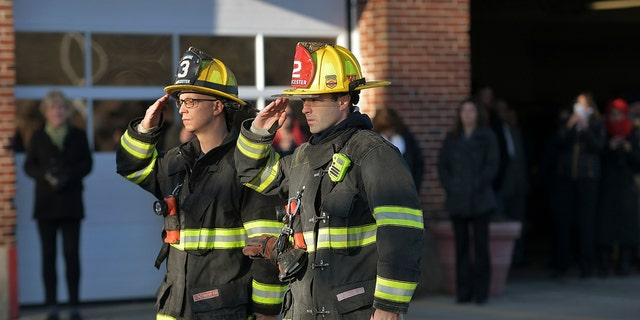 Two Firefighters salute at Grove Street Fire Station, after putting the flag at half staff after Lt. Jason Menard died in an overnight fire Wednesday, Nov. 13, 2019 in Worcester, Mass.