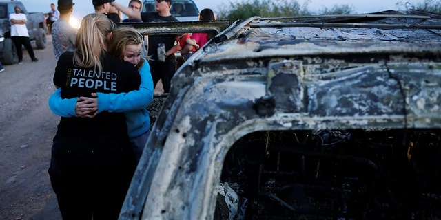 Relatives of slain members of Mexican-American families belonging to Mormon communities react next to the burnt wreckage of a vehicle where some of their relatives died in Sonora state.