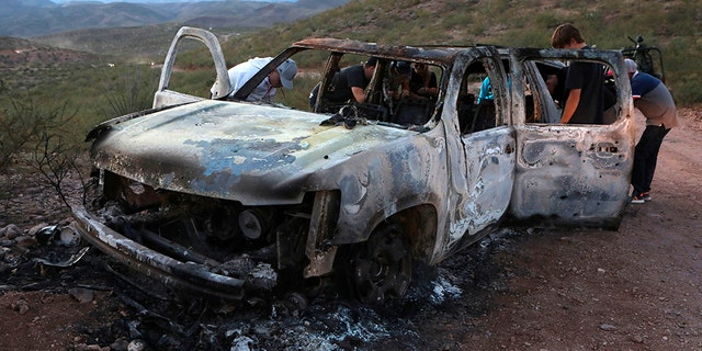 Members of the Lebaron family watch the burned car where part of the nine murdered members of the family were killed during a suspected cartel ambush in the Sonora mountains in Mexico. (AFP/Getty)