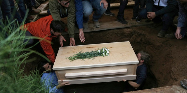 The coffin that contains the remains of 12-year-old Howard Jacob Miller Jr. is lowered into a grave at the cemetery in Colonia Le Baron, Mexico, on Nov. 8, during a burial service for Rhonita Miller and four of her young children who were murdered by drug cartel gunmen.