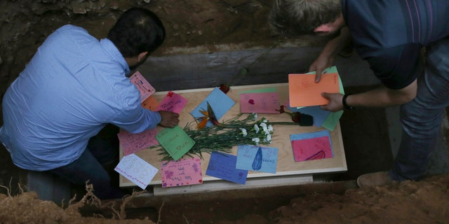 Men arrange personal notes on the casket containing the remains of 12-year-old Howard Jacob Miller Jr., at the cemetery in Colonia Le Baron, Mexico, Friday, November 8, 2019, during a funeral service for Rhonita Miller and four of her small children, who were murdered by drug cartel gunmen. (AP Photo / Marco Ugarte)
