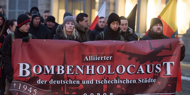 Right-wing extremists hold up a banner reading 'Alliierter Bombenholocaust' (lit. 'Allied Bombing Holocaust') during a so-called funeral march in Dresden, Germany, 11 February 2017. (Photo by Sebastian Kahnert/picture alliance via Getty Images)
