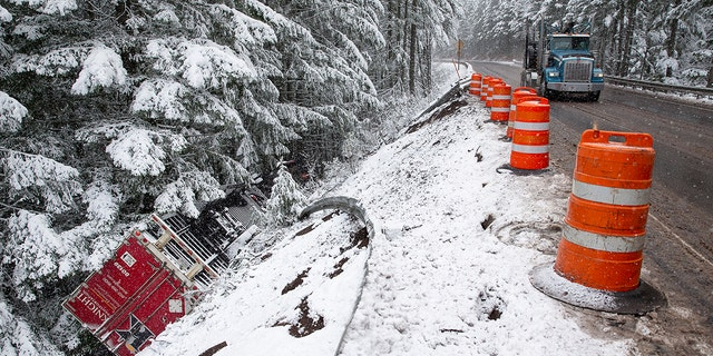 A tractor-trailer flipped over on Highway 58, east of Oakridge, Ore., under snowy and windy conditions Monday.