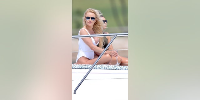 Pamela Anderson poses in a white swimsuit for a photo shoot on the Gold Coast