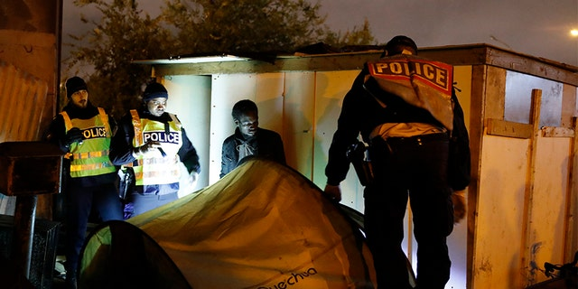Police officers evacuate a migrant from a camp on Thursday in Paris. (AP)