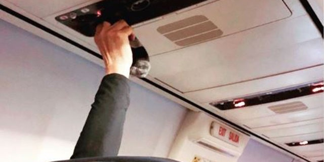 """""""Drying sweaty socks using the air vent,"""" text over the image of the passenger holding the socks read on Instagram."""