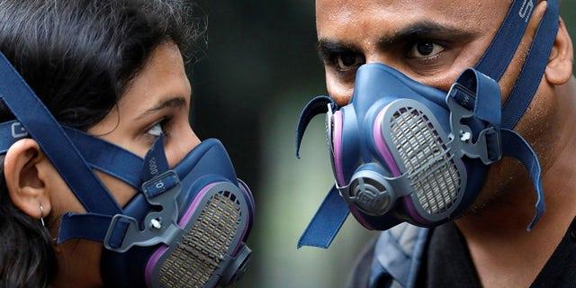 People wear masks on a smoggy evening in New Delhi, India, October 31, 2019. REUTERS/Anushree Fadnavis - RC1AF59327B0