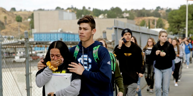 FILE - This Nov. 14, 2019 file photo shows students being escorted out of Saugus High School after a shooting on the campus in Santa Clarita, Calif.(AP Photo/Marcio Jose Sanchez, File)