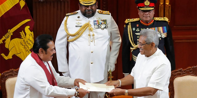 Sri Lanka's President Gotabaya Rajapaksa, right, accepts official documents from his brother Mahinda Rajapaksa after appointing him as prime minister at the presidential secretariat in Colombo, Sri Lanka, on Thursday. (AP)